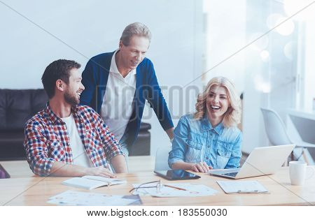 Positive department. Positive delighted colleagues sitting in the office and working on the project while expressing joy