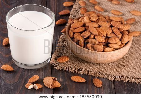Almond milk in a glass and almonds in a bowl on dark wooden background.