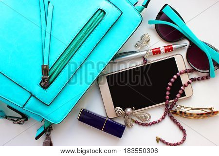 Objects of female life on a white table, phone, brooch, lipstick, glasses, beads, hair pin,  lady's bag