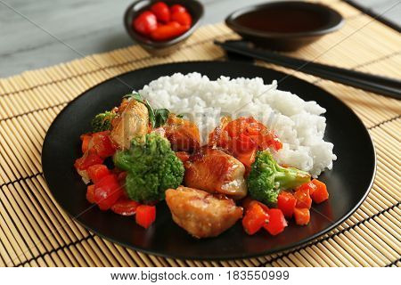Chicken stir fry with rice and chopsticks on table