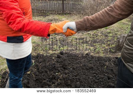 handshake on the background of the soil men and women in work gloves.