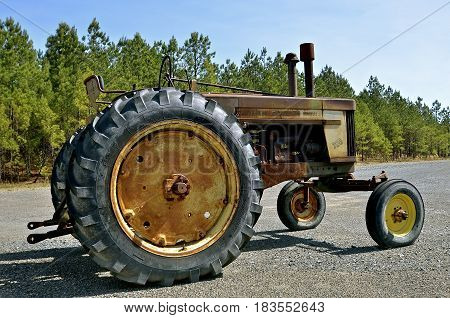AMITY, ARKANSAS, April 7, 2017: The old rusty parked 720 John Deere tractor is a product of John Deere Co, an American corporation that manufactures agricultural, construction, forestry machinery, diesel engines, and drive trains