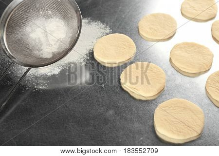 Fresh dough for cookies and sieve on table