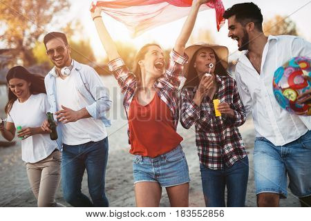 Happy group of young friends having fun on beach in summer