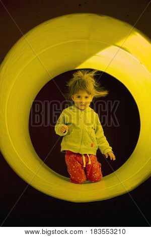 Child enjoys climbing through a tunnel in a children's playground outdoors.