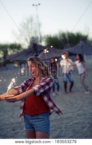 Group of happy friends having fun on beach at night playing with sparklers