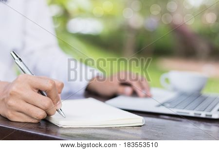 Business woman write on notebook outdoor in coffee shop.