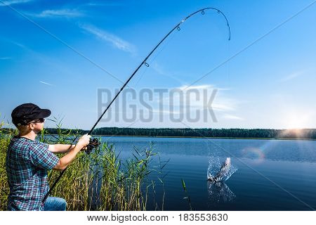 Angler holds a fishing rod with a reel.