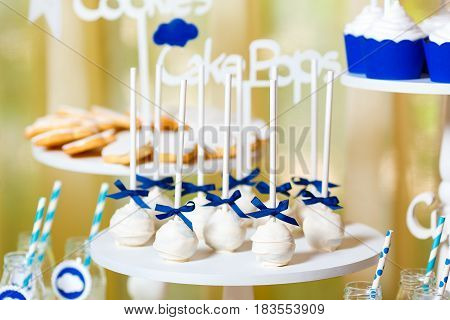 Candy bar on baby's christening party with a lot of different candies and beverages. Decorated in blue colors clouds theme indoor