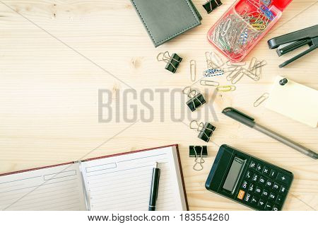 Office desk table with book planner pen calculator wallet pencil ruler stapler paper clips clamps sharpener. Top view with copy space flat lay. Business background.