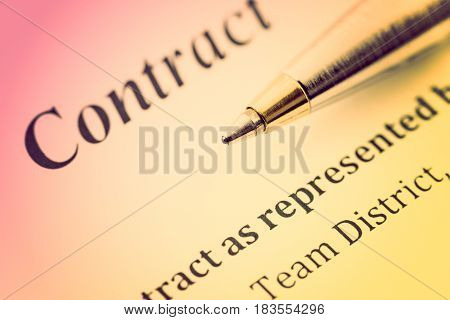 Colorful gradient style : Blue ballpoint pen on a contract. A contract is a voluntary arrangement between two or more parties that is enforceable by law as a binding legal agreement.
