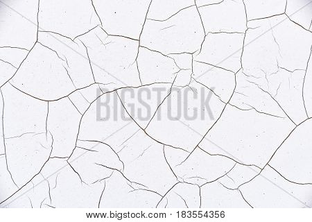 Close up view of white and thick cracked paint on an old traffic signpost located near a highway road. A symbol of a disunited or lacking unity. Abstract textured background.