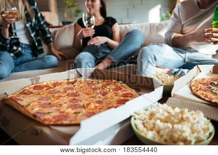 Group of happy young people eating pizza, drinking wine and beer on sofa at home