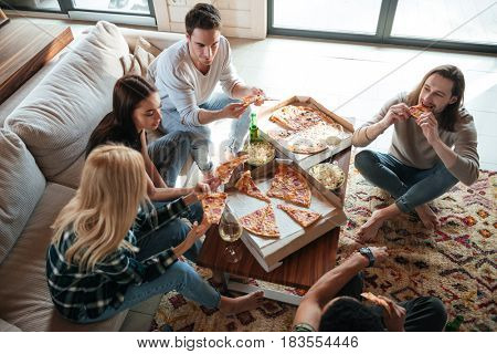 Top view of a five friend are sitting on sofa and eating pizza in house