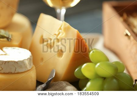 Different types of cheese and grapes, closeup