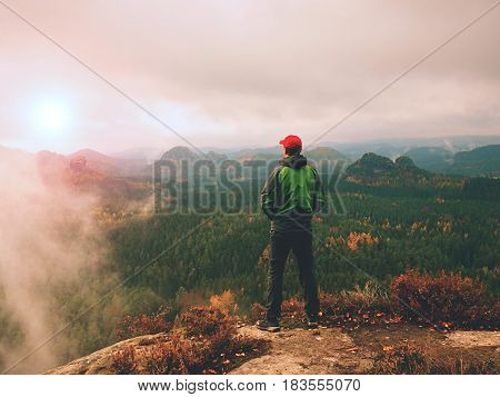 Man Tourist Stay On Sharp Rock Peak. Alone Hiker In Red Cap And Green Jacket  Enjoy View