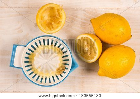 Freshly Squeezed Lemon With Strainer Above Wooden Background