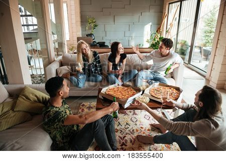 Group of young cheerful friends hanging out together at home with pizza and beer