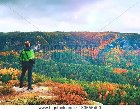 Ginger Hair Man Takes Photos With Smart Phone On Rocky Peak Above Autumnal Valley.