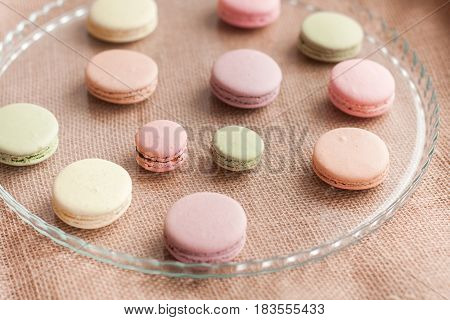 Closeup of colorful macaroons on the glass plate on sacking background
