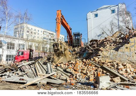 Tyumen, Russia - April 6, 2015: Destroyed two-storeyed barrack at address Holodilnaya street 88. Excavator loads construction garbage from demolished house into truck