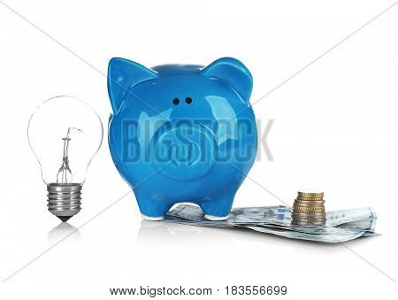 Cute blue piggy bank with money on white background