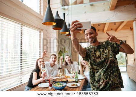 Cheerful african young man taking selfie with his friends at the table at home