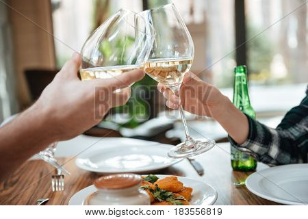 Close up portrait of a female and male hands toasting with glasses of white wine over table