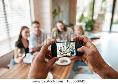 Closeup of man taking pictures of his friends with cell phone eating at the table at home