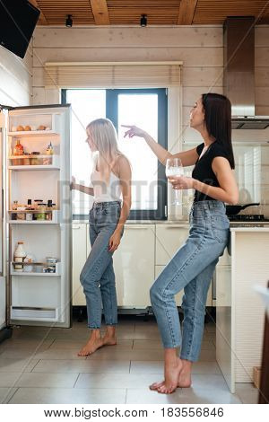 Vertical image of a two women standing on  kitchen and looking at the fridge. Side view