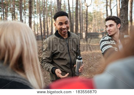Photo of cheerful group of friends standing outdoors in the forest. Looking aside and talking.