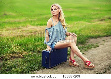 attractive sexy woman with a suitcase outdoor. portrait of a blonde stylish girl