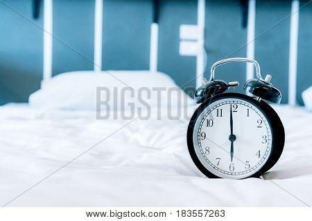 Retro alarm clock on white bed in wake up time morning.