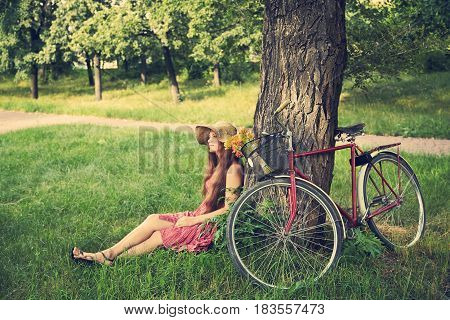 young woman in a hat with a bike sitting in the park near the tree . Active people. Outdoors