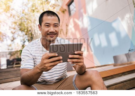 Portrait of a casually dressed young Asian man smiling and using a digital tablet while sitting alone on some stairs outside