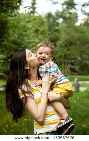 outdoor portrait of mother and son on green background. child and mom walk in the summer park
