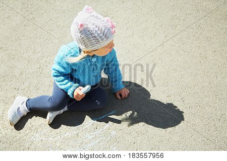 little girl draws chalk on asphalt. child playing in the open air in the summer