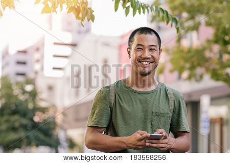 Portrait of a casually dressed young Asian man smiling while standing outside on a city street sending a text message on his cellphone