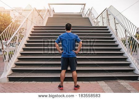 Rearview of a man standing with his hands on his hips at the bottom of a set of stairs while out for a city run