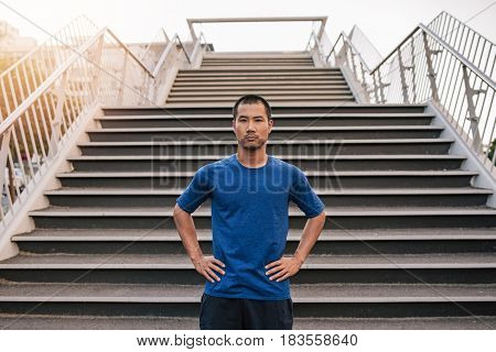 Portrait of a focused young man with his hands on his hips standing at the bottom of stairs while out for a city run