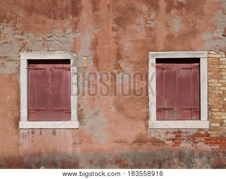 vintage distressed ochre painted wall with red wooden shutters and white window frames