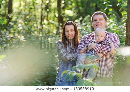 Young happy family: father, mother and their son having fun together outdoor in the forest. Pretty little son on father hands. Parents and son look happy and smile. Happiness and harmony in family life. Family fun outside. Concept of happy family relation