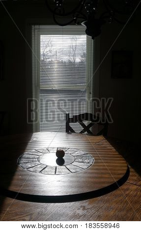 An orange sits in the center of a lazy Susan dining table in front of a window in the dining room of an historic Victorian home in Harbor Springs, Michigan.
