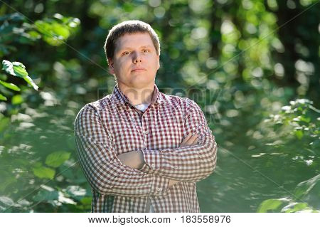 Closeup of serious young man in checkered shirt standing in forest and looking at camera. Outdoor portrait.
