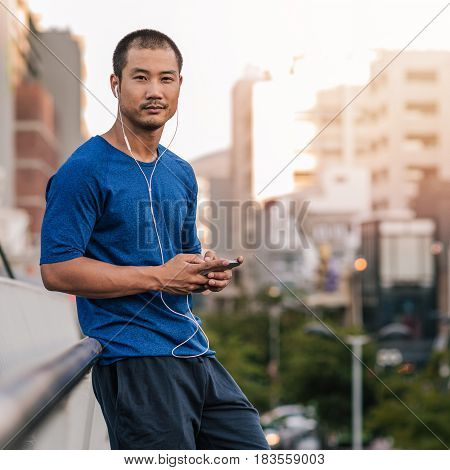 Square portrait of a young Asian man in sportswear standing on a bridge listening to music on phone while out for a city run