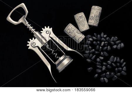 Pine nuts, corkscrew and cork on a dark background