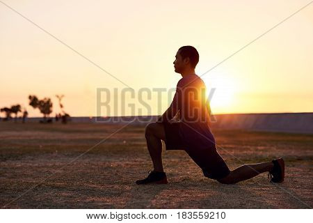 Focused and fit young Asian man stretching his legs before going for a solo run outside in the early morning