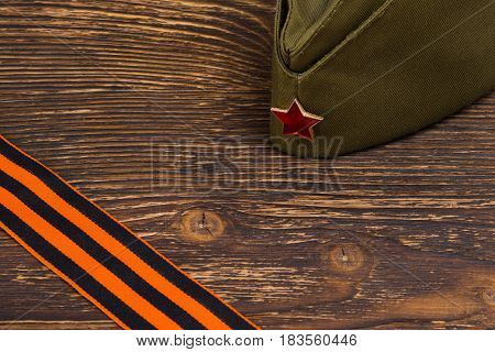 Military cap on a wooden table and place for inscription and St. George's ribbon