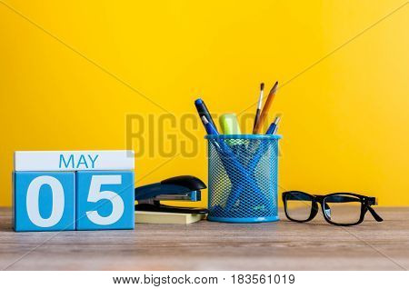 May 5th. Day 5 of month, calendar on business office table, workplace at yellow background. Spring time.