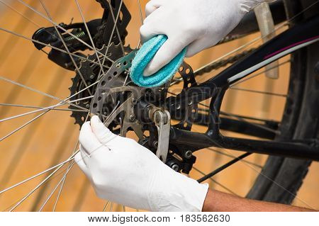 Closeup hand wearing white glove holding sponge rubbing on metal bicycle chain, mechanical repair concept.
